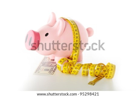 Diet price concept. Piggy bank with measuring tape and dollars - stock photo