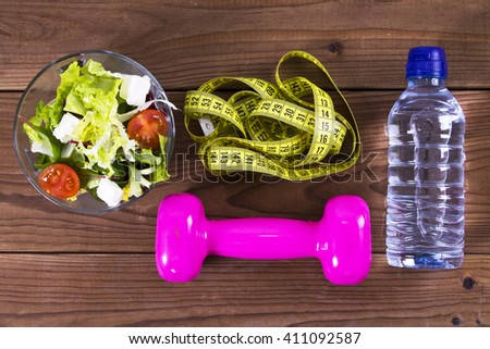diet: salad, tape measure and dumbbells - stock photo