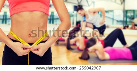 diet, sport, fitness and heath concept - close up of female hands measuring waist with measuring tape - stock photo