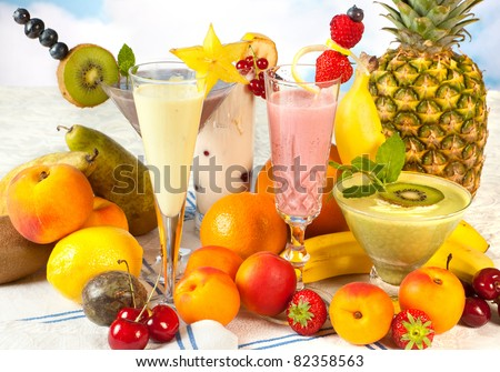 Diet table filled with summer fruits and colorful smoothies - stock photo