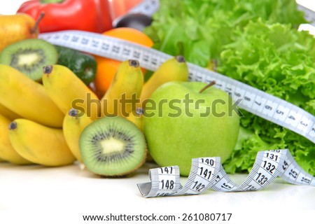 Diet weight loss breakfast concept with tape measure organic green apple salad bananas kiwi avocado grapefruit red pepper pear on a white background - stock photo