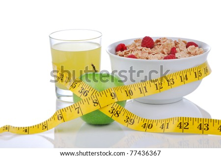 Diet weight loss concept with tape measure green and organic green apple, corn healthy rice and wheat flakes with fresh raspberries and carrot juice on a white background - stock photo