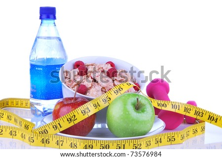 Diet weight loss concept with tape measure red and organic green apple, corn healthy rice and wheat flakes with fresh raspberries and carrot juice on a white background - stock photo