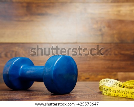 Diet weight loss fitness health care concept with dumbbell, measure tape on wood background. Diet heathy items for sport, fitness, healthcare, workout. Measurement tape metric ribbon and dumbbell. - stock photo