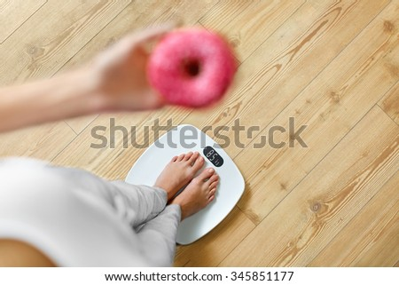 Diet. Woman Measuring Body Weight On Weighing Scale Holding Donut. Sweets Are Unhealthy Junk Food. Dieting, Healthy Eating, Lifestyle. Weight Loss. Obesity. Top View - stock photo
