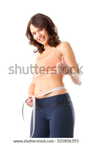 Diet - young woman is measuring her waist with measuring tape - stock photo