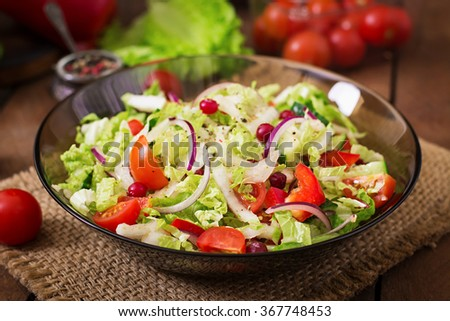 Dietary salad with fresh vegetables (tomato, cucumber, Chinese cabbage, red onion and cranberries) - stock photo