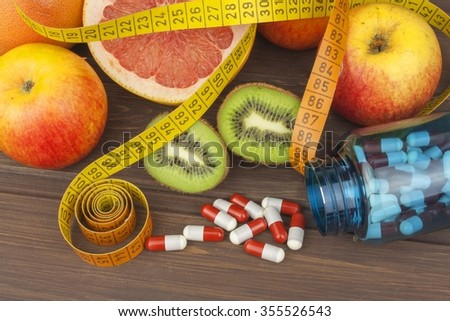 Dietary supplements for weight loss. Red grapefruit and fruit for weight loss. Fresh dietary food for athletes. Fruit on a wooden table.Balanced diet. Assortment of exotic fruits. - stock photo