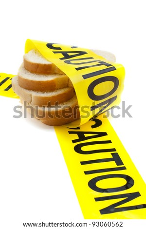 Dietary warning or gluten/wheat allergy warning (Slices of bread wrapped in yellow caution tape) - stock photo