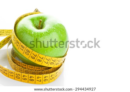Dieting concept. Green apple with measuring tape on white background - stock photo