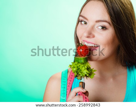 Dieting, healthcare and weight loss concept. Sporty girl fitness woman with measuring tape on neck and holding fork with fresh mixed vegetables on green blue background. Studio shot. - stock photo