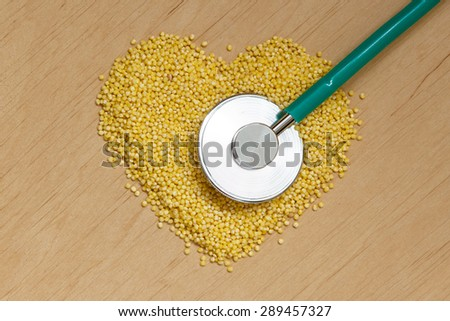 Dieting healthcare concept. Millet groats heart shaped and stethoscope on wooden surface. Healthy food for preventing cardiovascular disease - stock photo