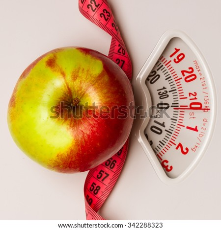 Dieting healthy eating slim down concept. Closeup apple with measuring tape on weight scale - stock photo