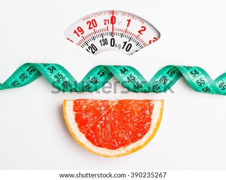 Dieting healthy eating slim down concept. Closeup grapefruit slice with measuring tape on white weight scale - stock photo