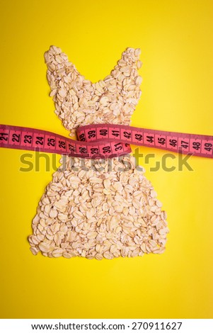 Dieting healthy eating slim down concept. Female dress shape made from oatmeal with measuring tape around thin waist on yellow - stock photo