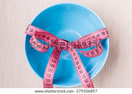 Dieting healthy lifestyle and slim body concept. Pink measuring tape around empty blue bowl on table, top view - stock photo