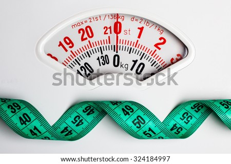 Dieting weightloss slim down concept. Closeup measuring tape on white weight scale - stock photo