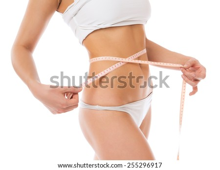 Dietting weight loss concept. Slim woman measuring waist with tape measure isolated on white background
