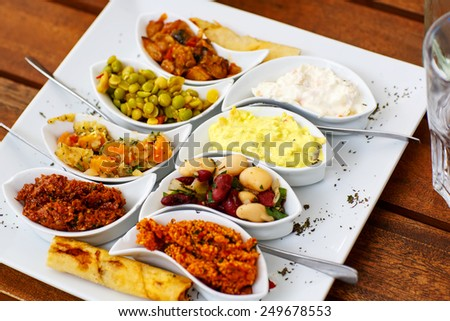Differen appetizer and anti pasti on white plate in cafe or restaurant - stock photo