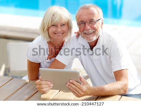 Different aged couple using a tablet pc outside - stock photo