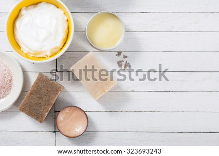 different bath salts, bees wax , makeup base, powder compact, soaps and cosmetic creams on white wooden background - stock photo