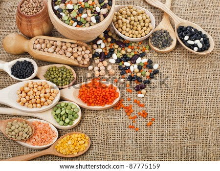 different beans, legumes, peas, lentils in spoon on the sackcloth background - stock photo