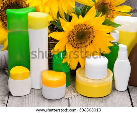 Different body care cosmetics and sunflowers in wicker basket on old wooden planks. Set of natural skincare cosmetic products - stock photo