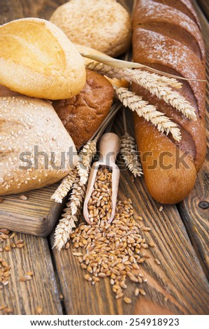 Different bread and wheat on the wooden table - stock photo