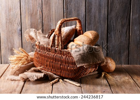 Different bread in wicker basket on table on wooden background - stock photo