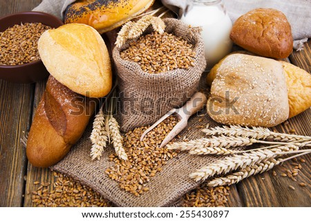 Different bread, wheat and milk on a wooden table - stock photo