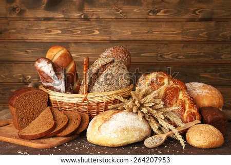 Different bread with ears and sunflower seeds on wooden background - stock photo