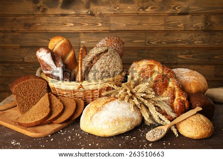 Different bread with ears in basket on wooden background - stock photo