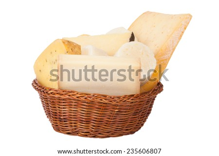 Different cheeses and a bunch of parsley lying in a wicker basket isolated on white background - stock photo