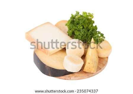 Different cheeses and a bunch of parsley lying on a board isolated on white background - stock photo