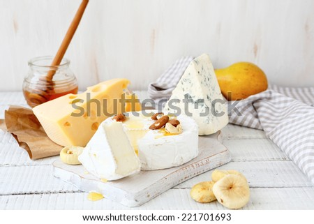 Different cheeses on a cutting board, delicious food - stock photo