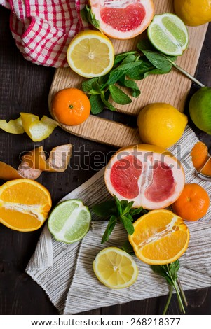 Different citrus fruits including lemon, grapefruit, lime, orange on the wooden chopping board  - stock photo