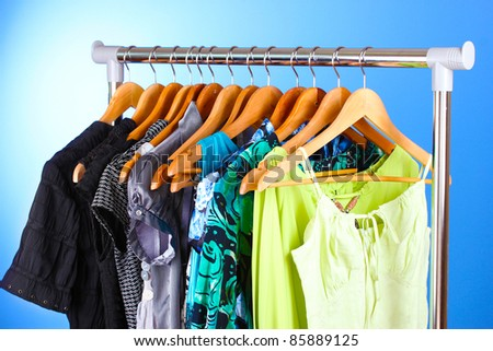 different clothes on wooden hangers on blue background - stock photo