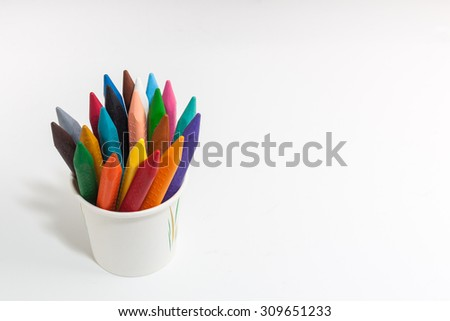 Different colors of crayon pencils in a cup on white background - top view - stock photo