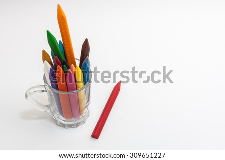 Different colors of crayon pencils in a glass on white background - top view - stock photo