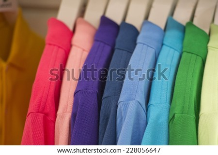 different colors polo shirt on display stand - stock photo