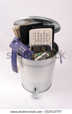 different computer parts and phone in trash can - stock photo