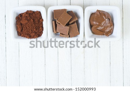 different conditions of chocolate, white wooden table background - stock photo