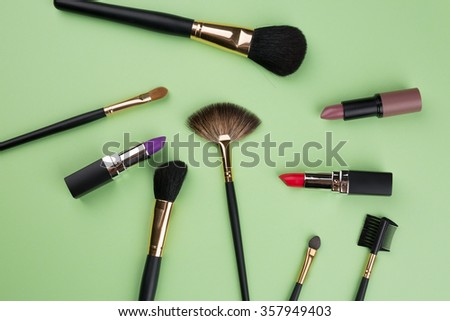 Different cosmetics on green background - stock photo