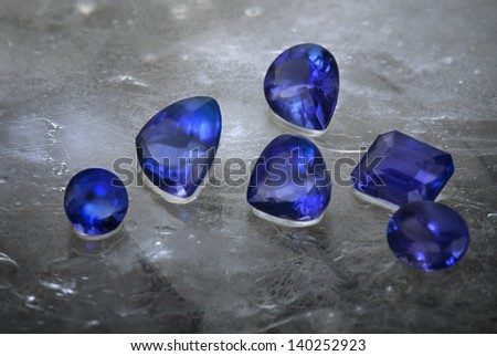Different cuts of Tanzanite isolated on grey ice background. - stock photo