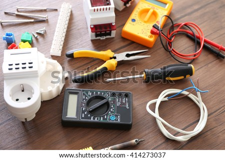 Different electrical tools on wooden table, top view - stock photo