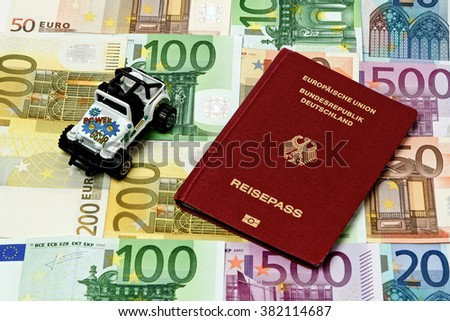 Different euro bills 500 200 100 50 Euro banknotes lying on a table. On top of the money lies a car and a passport - stock photo