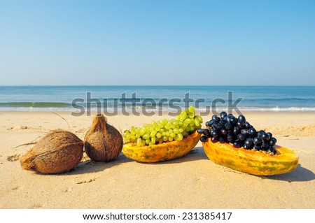Different exotic fruits on the tropical beach - stock photo