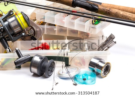 different fishing tackles - rod, reel, line and lures in box on white background - stock photo