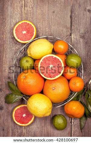 Different fresh citrus fruit in a basket on old wooden background. Top view (Toning) - stock photo