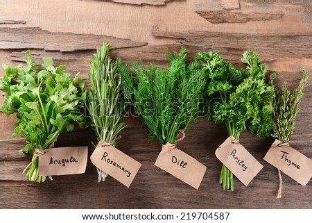 Different fresh herbs on wooden background - stock photo